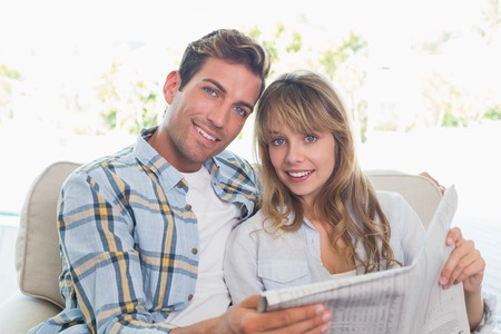 Loving happy young couple reading newspaper on couch at home photo