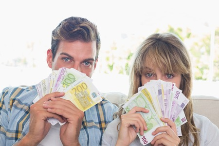 fanned: Close-up portrait of a young couple holding fanned out Euro notes at home