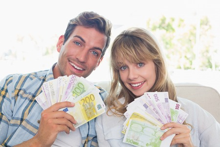 Close-up portrait of a young couple holding fanned out Euro notes at home photo