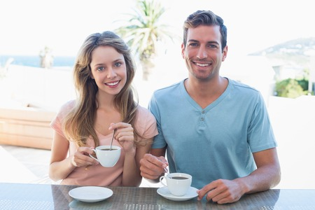 Happy young couple having coffee at table in the house photo