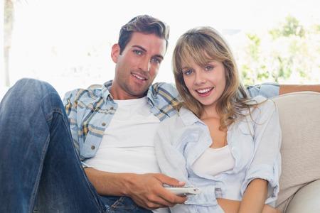 pareja viendo tv: Pareja joven viendo la televisi�n en el sof� en la sala de estar en casa