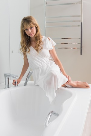 Beautiful young woman sitting on the edge of bath tub in the bathroom at home photo
