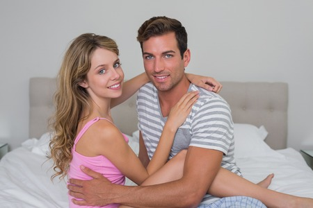 Portrait of a happy relaxed young couple sitting in bed at home photo