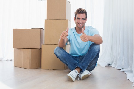 relocating: Portrait of a young man gesturing thumbs up with cardboard boxes in new house