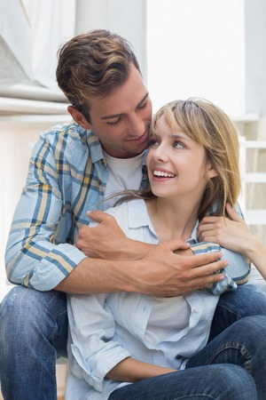 Portrait of a loving young man embracing woman at home photo
