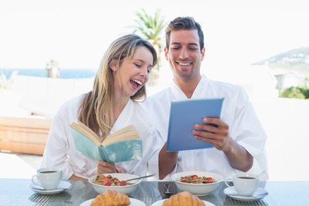 Cheerful young couple with book and digital tablet on breakfast table at home photo