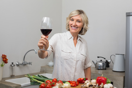 woman drinking wine: Portrait of a happy mature woman with vegetables and wine glass in the kitchen at home