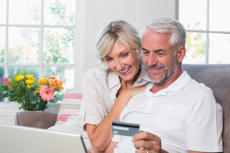 Happy mature couple doing online shopping through laptop and credit card at home photo