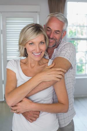 mujer de espaldas: Hombre maduro que abraza sonriente desde atr�s en casa