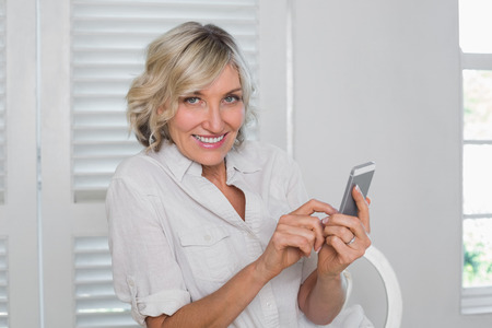 relaxed woman: Portrait of a relaxed mature woman text messaging at home