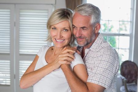 mujer de espaldas: Hombre maduro abrazando a una mujer feliz de detr�s en casa
