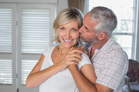 mujer de espaldas: Hombre maduro besando a una mujer feliz de detr�s en casa