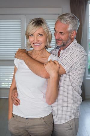 mujer de espaldas: Hombre maduro abrazando a una mujer feliz por detr�s en casa