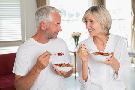 eating breakfast: Happy loving mature couple looking at each other and having breakfast at home