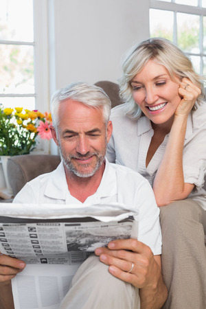 Happy mature couple reading newspaper at home photo