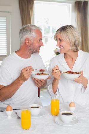 幸せな熟女カップル、お互いを見て、家庭で朝食を持っていることを愛する