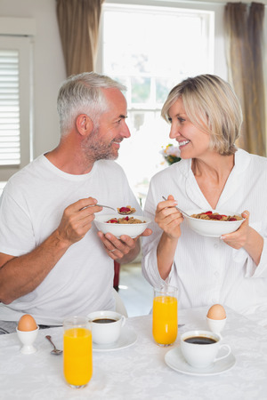 Happy loving mature couple looking at each other and having breakfast at home