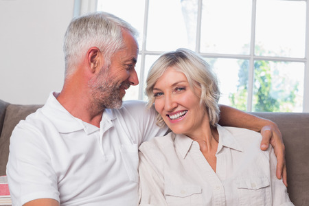 Portrait of a relaxed happy mature couple sitting on couch at home Фото со стока