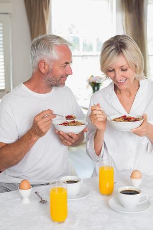 幸せな、リラックスした大人のカップルの家で朝食