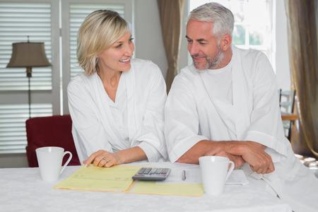 カジュアルな大人のカップル ホーム手形とテーブルで電卓に座っています。 写真素材