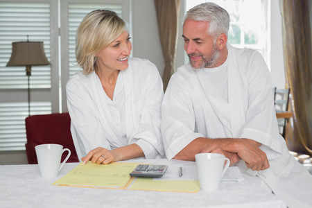 figuring: Casual mature couple sitting with home bills and calculator at table Stock Photo