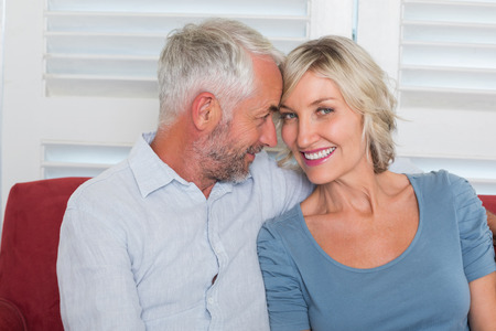 Relaxed smiling mature couple sitting on couch at home Reklamní fotografie