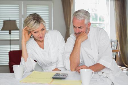 ホーム手形とテーブルで電卓に座っている思慮深い大人のカップル 写真素材