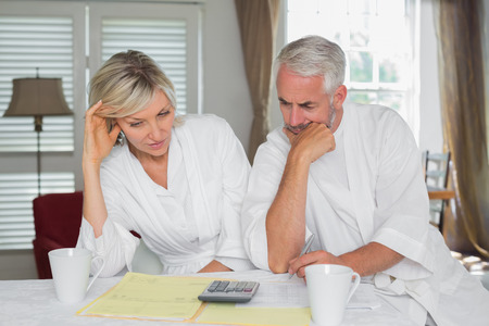 Thoughtful mature couple sitting with home bills and calculator at table Stock Photo - 28072783
