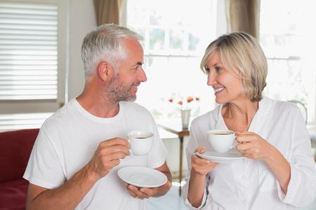 中高年カップルを浮かべて家庭でお互いを見てコーヒー カップ