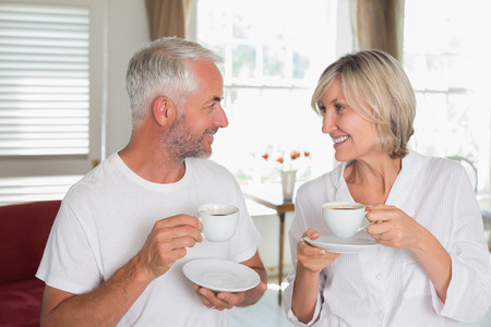 Smiling mature couple with coffee cups looking at each other at home Фото со стока