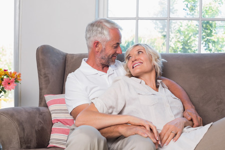 Relaxed smiling mature couple sitting on couch at home Фото со стока