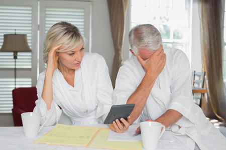 Worried mature couple sitting with home bills and calculator at table