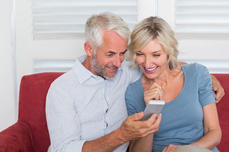 自宅のテキスト メッセージを読む大人のカップルの笑顔