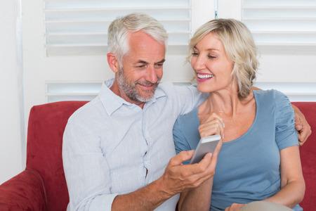Smiling mature couple reading text message at home Фото со стока