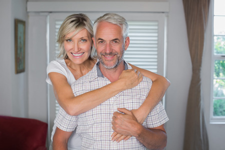 Portrait of a smiling woman embracing mature man from behind at home Reklamní fotografie