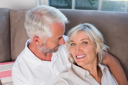 自宅のソファの上に座って幸せなリラックスした大人のカップルのクローズ アップ 写真素材