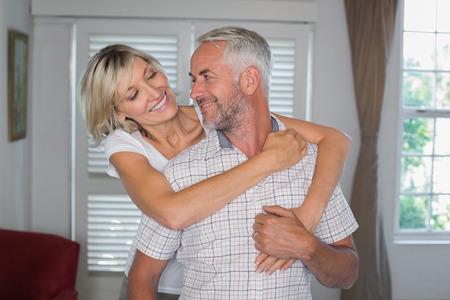 自宅で中年の男性を後ろから抱きしめる笑顔の女性の肖像画