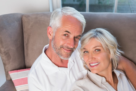 Close-up portrait of a happy relaxed mature couple sitting on sofa at home Фото со стока