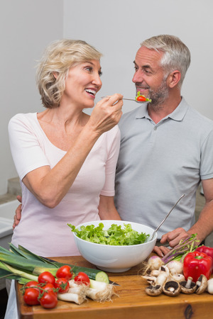 Happy woman feeding mature couple salad in the kitchen at home Фото со стока