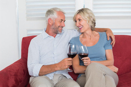 Happy relaxed mature couple toasting wine glasses in the living room at home