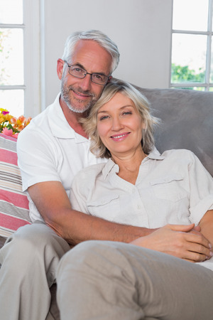 Portrait of a relaxed mature couple sitting on sofa in the living room at home