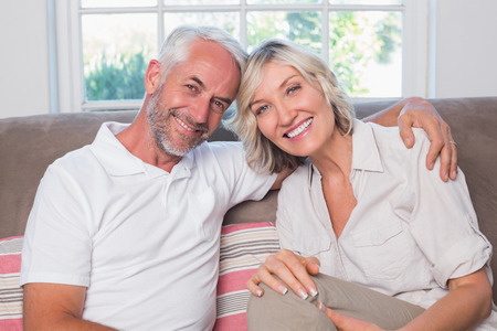 自宅のリビング ルームでソファの上に座ってリラックスした大人のカップルの肖像画