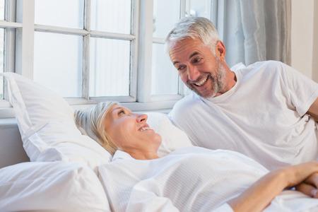 自宅のベッドで横になっている笑顔リラックスした大人のカップルの肖像画 写真素材