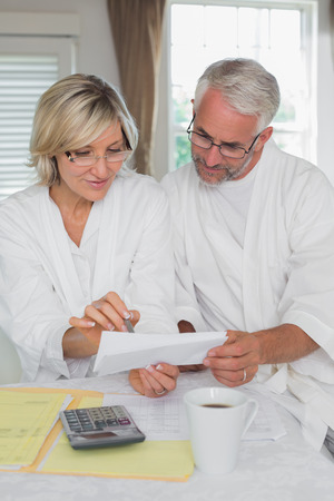 Casual mature couple sitting with home bills and calculator at table Reklamní fotografie
