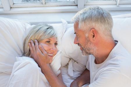 自宅のベッドで横になっている幸せな熟年カップルの高角のクローズ アップ 写真素材
