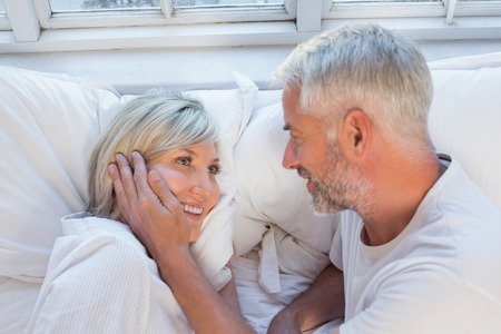 High angle close-up of a happy mature couple lying in bed at home Reklamní fotografie