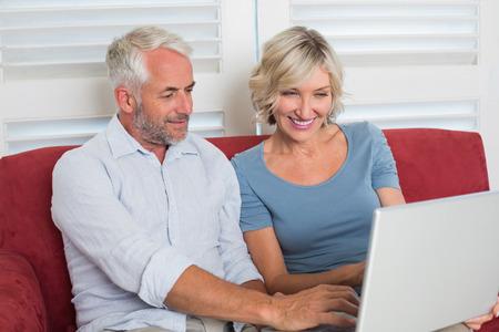 自宅の居間でノート パソコンを使用してカジュアルな成熟した女性の笑顔 写真素材