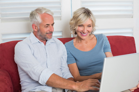 Smiling casual mature woman using laptop in the living room at home