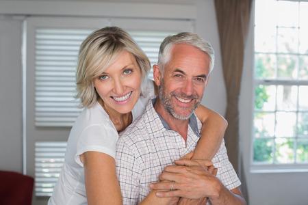 自宅で中年の男性を後ろから抱きしめる幸せな女の肖像 写真素材