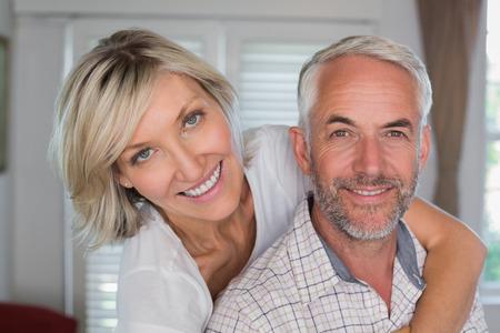 自宅で中年の男性を後ろから抱きしめる幸せな女のクローズ アップの肖像画